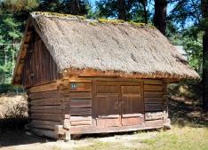 Niewielki, drewniany chlewik dla świń, z dachem krytym strzechą
