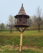 Drewniany gołębnik w kształcie ozdobnego domku, osadzony na wysokim słupie