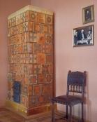 Fragment pomieszcznia w dworze z Drogini, z piecem kaflowym stojącym w rogu, obok krzesło, nad krzesłem dwa zdjęcia