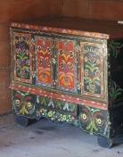 Drewniana skrzynia pomalowana w drobne kolorowe kwiaty