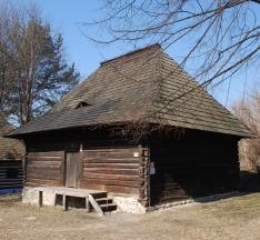 Drewniany budynek z czterospadowym dachem, krytym gontem