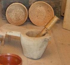 Naczynie wydrążone w drzewie, z drewnianym ubijakiem, stojące na drewnianej podłodze