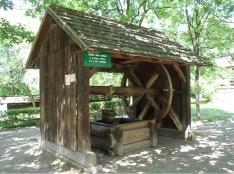 Drewniana studnia z dużym kołowrotem, przykryta dwuspadowym dachem