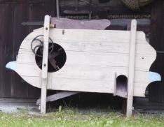 Drewniana maszyna do oczyszczania wymłóconego ziarna, stojąca na tle drewnianej chałupy