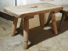 Niski drewniany stołek,  wspierający się na czterech nogach,  lekko skierowanych na zewnątrz